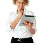 Businesswoman looking at tablet and thinking deep